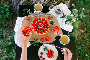 High angle cropped hands of woman eating strawberry cake on table in yardの写真素材 [FYI03755546]