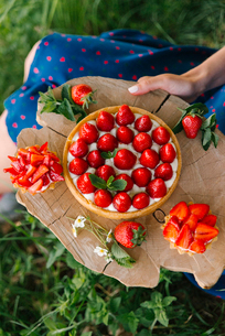 Midsection of woman holding strawberry cake on wooden board while sitting in yardの写真素材 [FYI03755549]