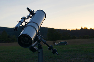 Astronomy telescope on grassy field against sky during sunsetの写真素材 [FYI03755665]