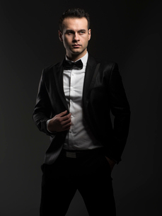 Handsome businessman in suit looking away while standing against black backgroundの写真素材 [FYI03755678]