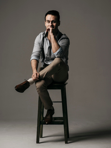 Portrait of handsome businessman sitting on stool against gray backgroundの写真素材 [FYI03755679]