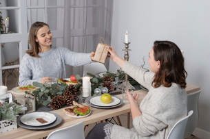 Woman giving Christmas present to female friend while having dinner at homeの写真素材 [FYI03755690]