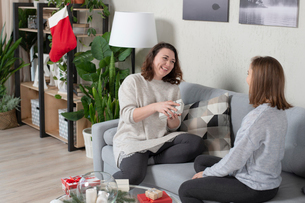 Happy woman opening Christmas present given by female friend while sitting on sofa at homeの写真素材 [FYI03755691]