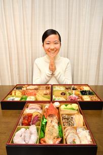 おせち料理を食べる女の子(正月、合掌)の写真素材 [FYI03755739]