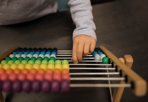 Cropped hand of girl using abacus on table at homeの写真素材 [FYI03755769]