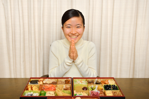おせち料理を食べる女の子(正月、合掌)の写真素材 [FYI03755772]