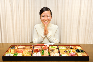 おせち料理を食べる女の子(正月、合掌)の写真素材 [FYI03755773]