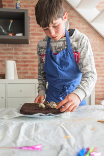 Boy decorating chocolate cake on table while standing against brick wall at homeの写真素材 [FYI03755788]