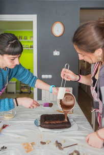 Mother with daughter making chocolate cake on table at homeの写真素材 [FYI03755793]
