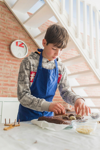 Low angle view of boy decorating chocolate cake on table while standing against brick wall at homeの写真素材 [FYI03755799]