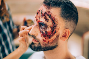 Man with makeup on his face with wounds and blood.の写真素材 [FYI03755881]