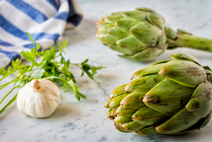 Artichokes, garlic and parsley on a marble counterの写真素材 [FYI03756015]