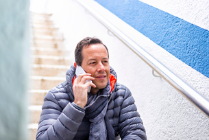 Man using a smartphone while sitting on a staircase outdoor.の写真素材 [FYI03756047]
