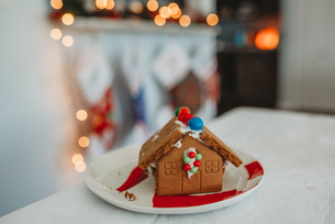 Gingerbread house with twinkle lights and stocking blurred in backgroundの写真素材 [FYI03756105]