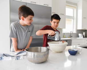Young boy watching older boy use a mixer in a modern kitchenの写真素材 [FYI03756424]