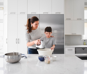 Mother helping young son use a hand mixer in a modern kitchenの写真素材 [FYI03756427]