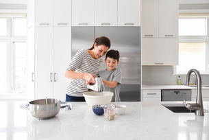 Mother helping young son use a mixer while cooking in a modern kitchenの写真素材 [FYI03756430]