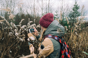 Girl taking pictures of nature on the phoneの写真素材 [FYI03756535]