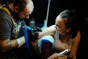 Young smiling woman at tattoo salon getting tattooed her armの写真素材 [FYI03756554]
