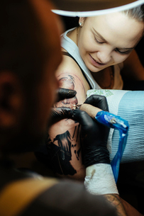 Young smiling woman at tattoo parlor getting tattooed her armの写真素材 [FYI03756557]
