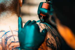 Professional Male Tattooer Makes A Tattoo On The Male Backの写真素材 [FYI03756560]