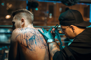 Male Tattoo Master In Black Gloves And Glasses Tattooing Male Back In Tattoo studioの写真素材 [FYI03756562]