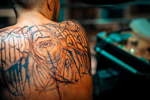 Professional male tattooer creating sketches for tattoo on the male back in tattoo studioの写真素材 [FYI03756564]