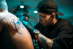 Male Tattoo Master In Black Cap And Glasses Tattooing Male Back In Tattoo Salonの写真素材 [FYI03756566]