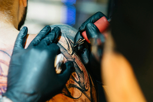 Closeup Of Male Tattoo Master In Black Gloves Tattooing Male Back In Salonの写真素材 [FYI03756567]