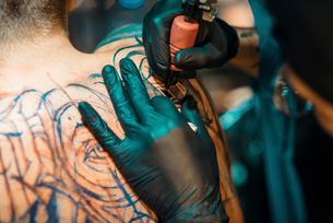 Closeup Of Male Tattoo Master In Black Gloves Tattooing Male Back In Tattoo Salonの写真素材 [FYI03756581]