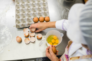 woman pastry chef adding eggs to graduated container while making cakesの写真素材 [FYI03756670]