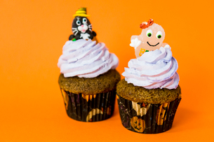 two funny halloween cupcakes with a cheshire cat and a ghost on creamの写真素材 [FYI03756692]