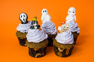 group of funny halloween monster cupcakes on an orange tableの写真素材 [FYI03756693]