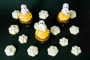 Funny scary cupcakes on a black bacground with meringue all aroundの写真素材 [FYI03756697]