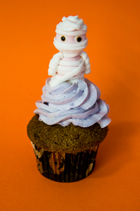 blueberry butter cream funny mummy cupcake with orange backgroundの写真素材 [FYI03756698]