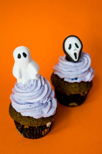 couple of funny halloween monster cupcakes on an orange tableの写真素材 [FYI03756699]