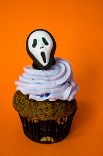 funny halloween monster mask cupcake on an orange backgroundの写真素材 [FYI03756704]