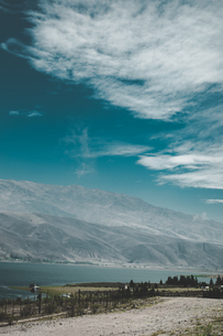 Vertical shoot of a road to lake on a backdrop of mountains.の写真素材 [FYI03757185]