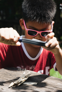 Boy burns dried leaf with Magnifying glassの写真素材 [FYI03757462]