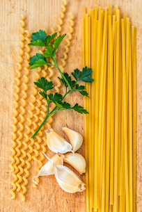 Pasta, parsley, and garlic on wooden boardの写真素材 [FYI03757724]
