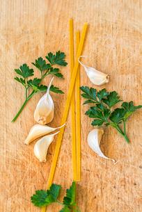 Pasta, parsley, garlic cloves on wooden board.の写真素材 [FYI03757725]