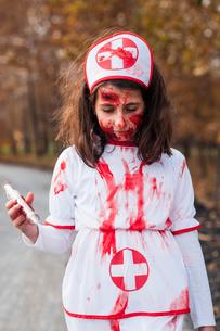 Girl dressed up in spooky bloody nurse costume for halloweenの写真素材 [FYI03757767]
