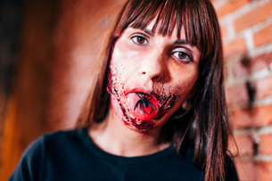 Woman with her face painted with terror wounds.の写真素材 [FYI03757788]
