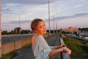 Attractive, charming young woman leans on bridge railingの写真素材 [FYI03757790]