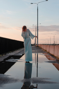 woman stands in a puddle on the bridgeの写真素材 [FYI03757816]