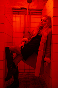 woman dressed standing in the shower, illuminated by red lightの写真素材 [FYI03757819]