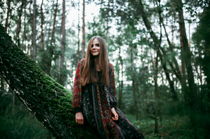 woman sitting on a tree in the forest and smilingの写真素材 [FYI03757830]