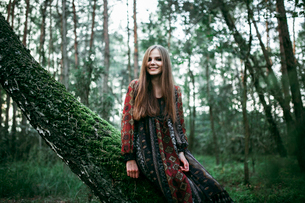 woman sitting on a tree in the forest and smilingの写真素材 [FYI03757831]