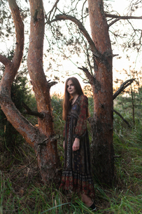 Caucasian girl stands in the middle of treesの写真素材 [FYI03757841]