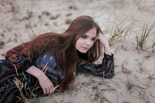 girl lying on the sand, leaning on the armの写真素材 [FYI03757846]